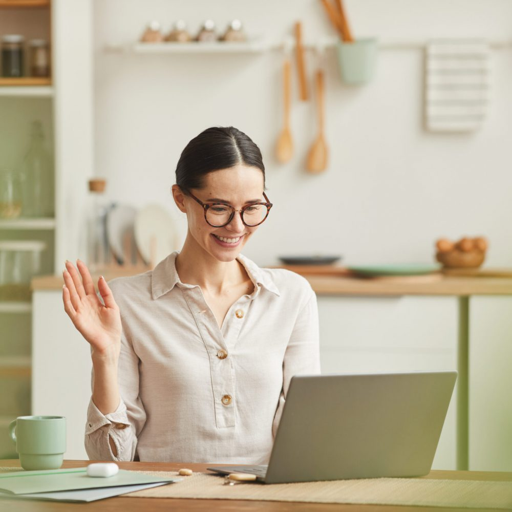 Warm-toned portrait of smiling young woman waving at camera during online meeting while working from home, copy space